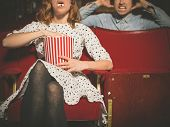 stock photo of annoying  - A young woman is eating popcorn loudly in a movie theater and is annoying the man sitting behind her - JPG