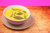 picture of curry chicken  - Hot and spicy chicken green curry on a pink background on a wood table top - JPG