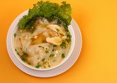 stock photo of glass noodles  - Glass noodle soup with chicken and beansprouts on an orange background - JPG