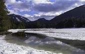 picture of snow clouds  - Mountain stream reflecting clouds with snow and mountains in the background - JPG