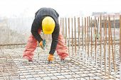 image of reinforcing  - construction worker making reinforcement with metal rebar rods at building site - JPG