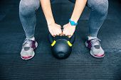 foto of kettles  - Closeup image of a woman working out with kettle ball at gym - JPG