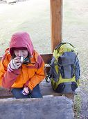 picture of thermos  - Girl with a backpack sitting at a wooden table and drinking from a thermos - JPG