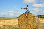 pic of haystack  - young boy sitting on haystack in the field smiling and pointing his hands aside as if calling to have fun with him - JPG