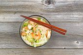 picture of glass noodles  - Top view image of Chinese noodle soup in clear glass bowl on top of rustic wood - JPG
