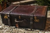 pic of paving stone  - Old closed locked retro vintage leather suitcase on stone paved surface closeup - JPG
