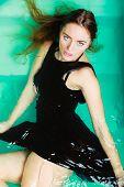 foto of sexuality  - Sexual posing woman in black dress in water - JPG