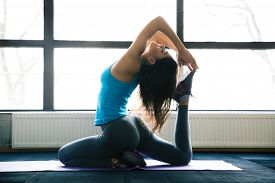 stock photo of sportswear  - Young woman doing yoga exercises on yoga mat at gym - JPG