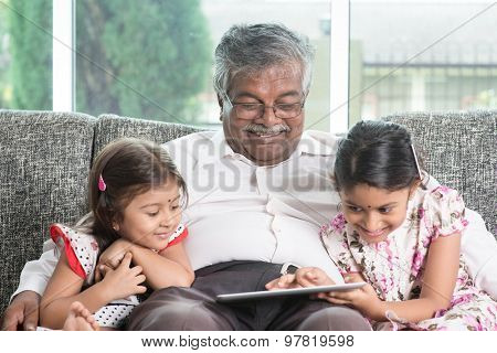 Modern technology concept. Grandparent and grandchildren using touch screen tablet computer. Portrai