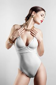 picture of monokini  - Sexy glamour model posing in white swimsuit on white background - JPG