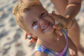 image of sun tan lotion  - Cute baby girl applying sun screen lotion for safe tan and skin care - JPG