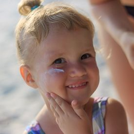 picture of sun tan lotion  - Cute baby girl applying sun screen lotion for safe tan and skin care  - JPG