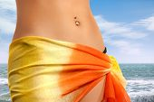 Closeup of a stomach of a young woman in colorful pareo on the beach