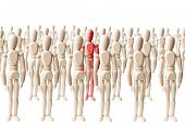 Large group of wooden dummies forming a crowd on white with different colored one among