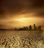 image of global-warming  - Global Warming and pollution theme with cracked land and the cityscape - JPG