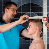 Physical Therapist Measuring Height Of Teenage Boy poster