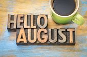 Hello August- word abstract in vintage letterpress wood type blocks against grunge wooden background poster