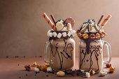 Chocolate  milkshake with ice cream and with whipped cream, marshmallow, sweet popcorn, cookies, waf poster