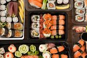 Assorted sushi set served in plastic boxes on wooden table poster