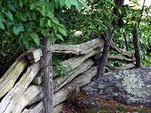Old Wooden Fence By A Large Rock