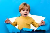 Surprised Boy Looking Through Hole In Paper Wall. Shocked Child Boy Making Hole In Paper. Adorable K poster
