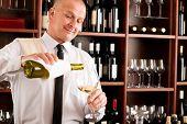 Wine bar happy waiter pour white wine in glass restaurant