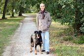 Senior Man zu Fuß mit seinem Hund in den Wäldern