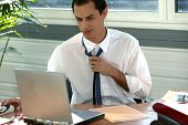stock photo of transpiration  - Stressed office worker loosening his tie - JPG