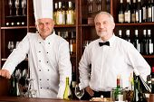 Chef cook and waiter smiling in restaurant wine bar