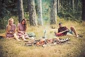 Girls Sitting Next To Campfire While Reading Books. Bearded Man Lying On Grass In Forest. Friends Ca poster