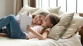 Cute Child Daughter Holding Book Reading To Mom In Bed poster