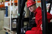 forklift driver worker in red uniform and safety helmet in storehouse portrait