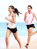 People running: couple runners training outdoors on beach. Young multiracial woman fitness model and