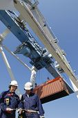 dock workers with large container-crane in background, commercial port