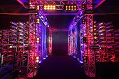 Multi-colored illuminated way with grid to boxing ring inside fight club; many lights