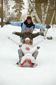 pic of toboggan  - Happy kids and their parents tobogganing in park - JPG