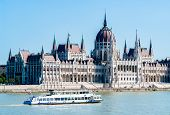 Hungarian Parliament Building In Budapest With White Cruise Tour Boat And Danube River In Foreground poster