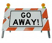 A road barrier reading Go Away tells you to stay back due to an area being closed or unwelcoming to