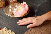 TCM la medicina tradicional China. Fumar moxa mini palo, flores y hierbas naturales en frascos de vidrio en