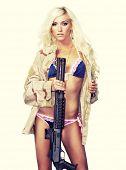 Sexy blond holding gun wearing army flak jacket