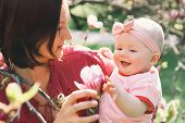 Loving Mother And Baby Girl Are Smelling Blooming Blossom Pink Magnolia Tree. Young Beautiful Mom An poster