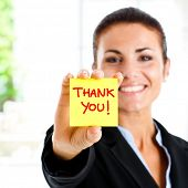 Happy businesswoman showing greetings on a post-it