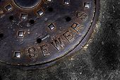 Man hole cover for sewer entry with iron grate on street in a city poster