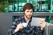 Serious Young Entrepreneur Checking Up Business News Over Morning Cup Of Coffee. Focused Guy In Casu poster