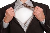 Businessman in classic superman pose tearing his shirt open to reveal blank copy space on chest