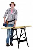 Woman sawing plank with band-saw