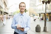 Smiling Businessman Using Tablet Computer in public space and looking on street