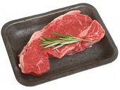 Raw sirloin beef steak in styrofoam packaging tray.