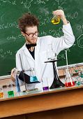 Mad professor stares at Bunsen flask with yellow liquid