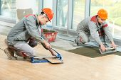Two industrial tiler builder worker installing floor tile at repair renovation work